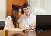 Young couple looking financial documents in laptop — Stock Photo