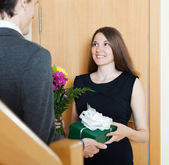 Girl giving flowers and gift — Stock Photo