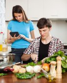 Man cooking food while woman reading eBook  — Stock Photo