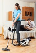 Wife cleaning and husband rests — Stock Photo