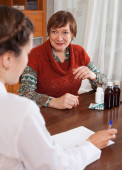 Senior woman complaining to  doctor about feels  — Stock Photo