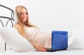 Uśmiechający się ładny blond ciąży z laptopa leżąc w łóżku na poduszkę — Zdjęcie stockowe