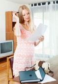 Long-haired pregnant woman looking  document — Stock Photo