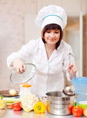 Cook woman in toque cooks in kitchen — Stock Photo
