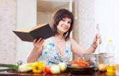 Jonge huisvrouw koken met kookboek — Stockfoto