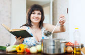 Positive woman cooking with cookery book  — Stockfoto