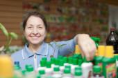Gardener chooses liquid fertilizer at  shop — Stock Photo