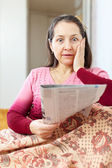 Wonderingly  woman having grief after readed   newspaper — Stock Photo