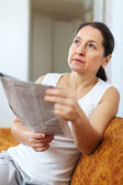 wistful  woman with newspaper   — Stock Photo