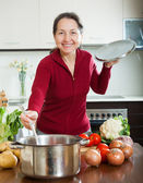 Happy mature woman cooking lent diet soup — Stock Photo