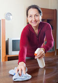 Mature  woman dusting wooden table   — Stock Photo