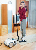 Happy mature woman cleaning with vacuum cleaner — Stock Photo