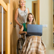 Social worker and invalid with laptop — Stock Photo #57463973