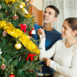 Couple decorating Christmas tree — Stock Photo #57467049