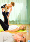 Instructor helps elderly to stretch — Stock Photo