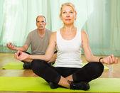 Elderly couple having yoga at home — Stock Photo