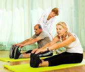 Yoga instructor showing asana to mature couple — Stock Photo