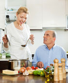 Woman cooking with husband in  kitchen — Stock Photo