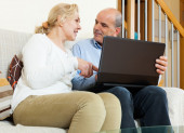 Smiling mature couple  with laptop — Stock Photo
