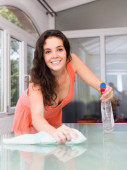Smiling brunette houswife cleaning  furniture — Stock Photo