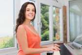 Happy girl playing piano at home — Stock Photo