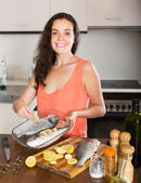 Woman cooking fish at home kitchen — Stockfoto