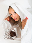 Girl smiling and eating chocolate in her bed — Stock Photo