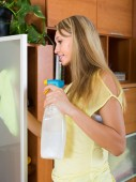 Blonde girl cleaning glass door of furniture — Zdjęcie stockowe