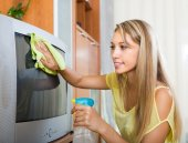 Blonde woman cleaning TV at home — Stock Photo