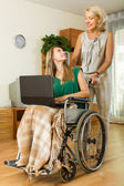 Social worker and invalid with laptop — Stockfoto