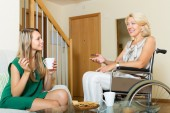 Female friend visiting disabled woman — Stock Photo