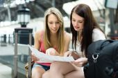 Two young women with baggage and map   — Stockfoto