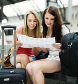 girls sitting at railroad station with map — Stockfoto