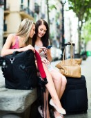 Two smiling girls with GPS navigator and baggage — Stock Photo