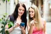 Two nice girls finding path with smartphone — Stockfoto
