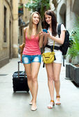 Two girls using  GPS navigator for find a way — Stockfoto