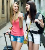 Two young girls with baggage heading to hotel — Stockfoto