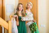 Women with food purchases at threshold  — Stock Photo