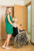 Girl helping handicapped woman — Stock Photo