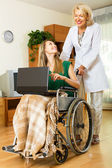 Girl in wheelchair  working on laptop  — Stock Photo