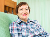 Portrait of happy senior woman relaxing in couch — Foto Stock