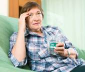 Pensioner with pills and glass of water — Stock Photo