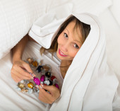 Woman secretly eating candy in bed  — Stockfoto
