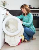 Ordinary girl using washing machine — Stockfoto