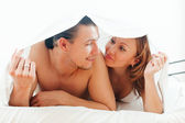 guy and woman  together under sheet on bed   — Stock Photo