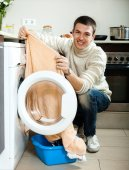 man putting clothes in to washing machine — Stock fotografie