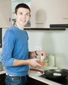 Handsome guy cooking frying squid — Zdjęcie stockowe