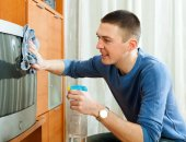 Ordinary guy woman dusting TV — Stock Photo