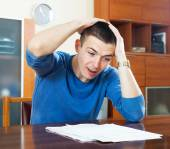 Sad shocked guy looking at document at home — Stock Photo