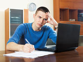 Sad guy  with laptop and financial documents — 图库照片